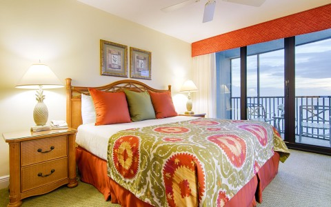 Room with king bed, warm colored bed comforter, wooden nightstands & balcony with beach view
