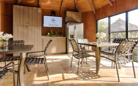 Dining lounge with metallic tables & chairs with window panel overlooking tiki hut & water