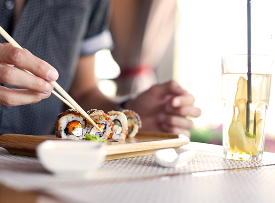 Man grabbing piece of sushi roll with chopsticks