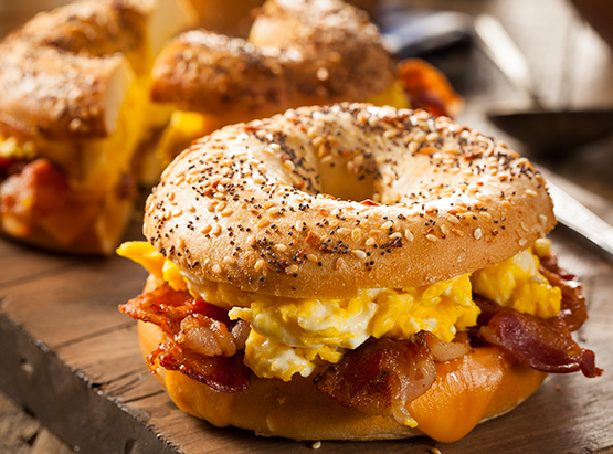 Two bagels with scrambled eggs & bacon on wooden board