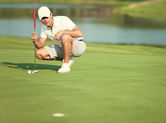 Man crouched down analyzing distance between golf ball & hole