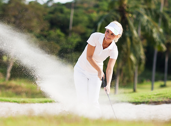 Woman standing in golf course sand pit with sand in the air