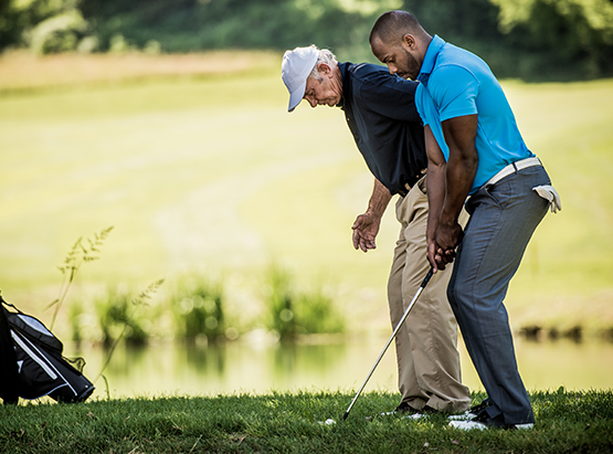 Old man teaching younger man how to hit golf ball