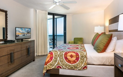 suite with king bed and sliding glass door that leads to balcony