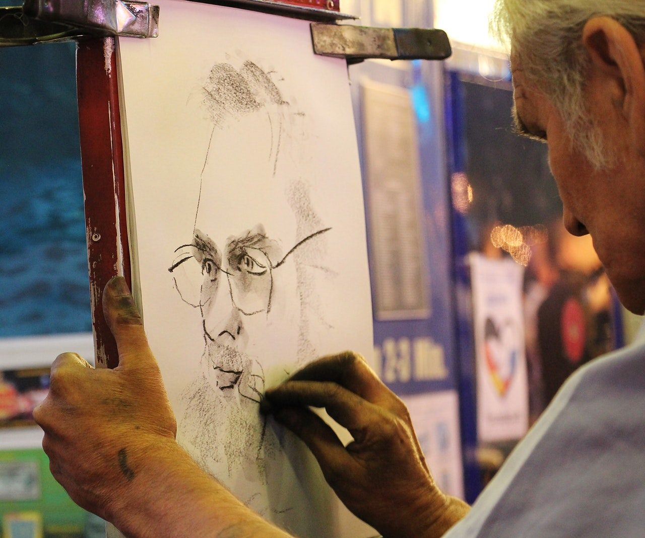an artist works on charcoal drawing