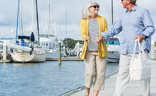 Older couple strolling along marina with boats docked