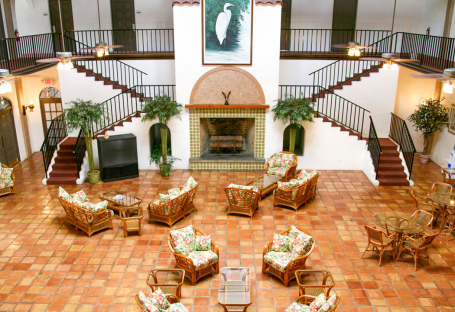 Aerial view of lobby area with wicker chairs, brown toned tiles & wooden stairs
