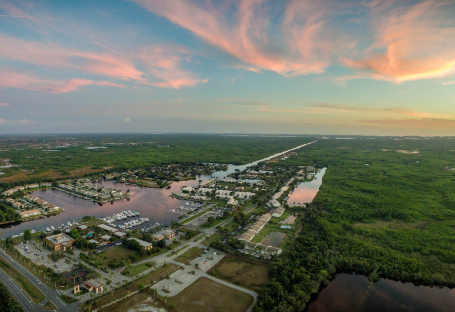 Aerial view of property surrounded by the everglades with sun setting in the back
