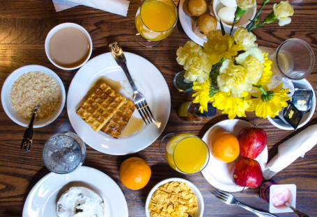 Aerial view of table with fruit, waffles, cereal, bagel & yellow flowers in the center
