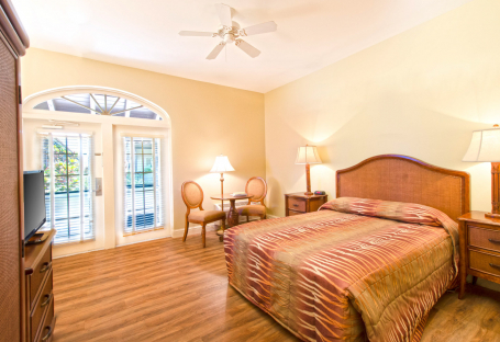 Room with king bed, wooden flooring, dresser & seating area next to window