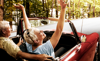 Older couple laughing as they ride in red convertible
