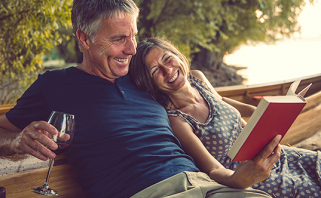Older couple enjoying book while sitting on outdoor wooden bench