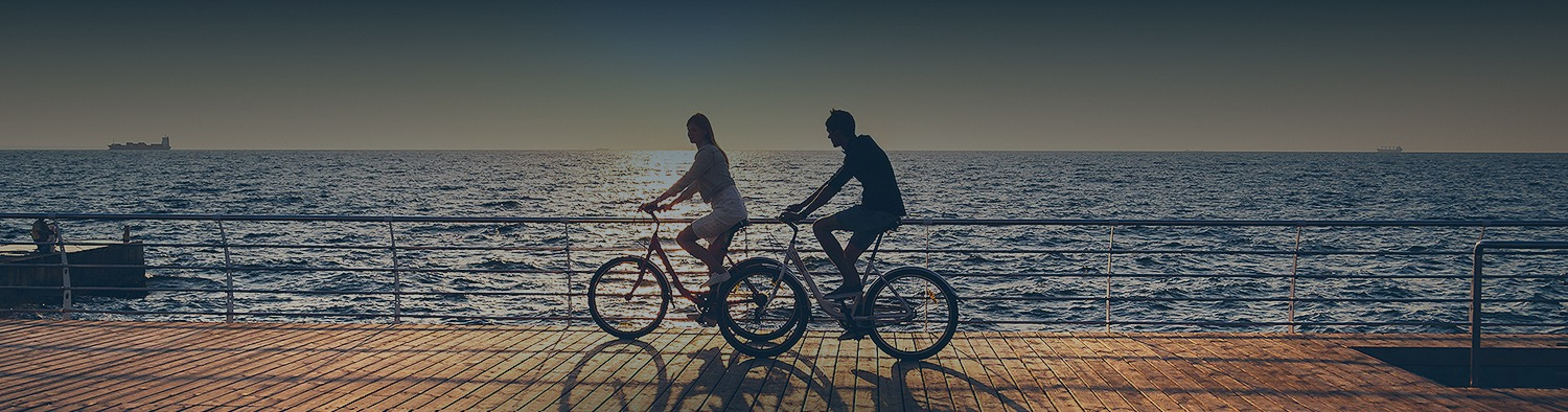 man and woman biking by the water