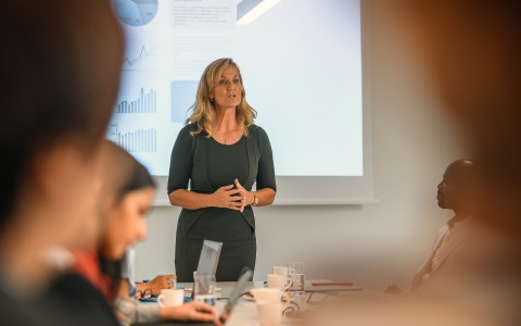 woman presenting to a group of colleagues