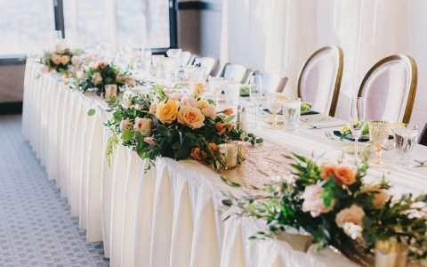 long table with white linens and flower centerpieces