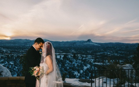 newlyweds kissing on top of mountain