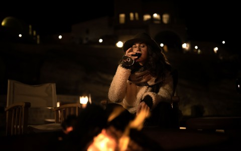 woman at night by a fireplace drinking wine