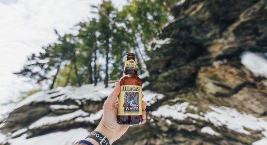 Allagash White in Mountains beverage being held in the air outside