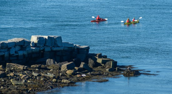 Two kayaks with people on ocean water close to rocky shore