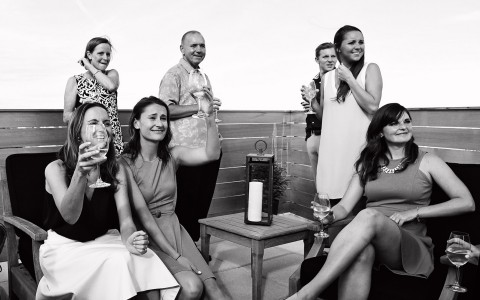 Black & white image of friends gathered on rooftop terrace