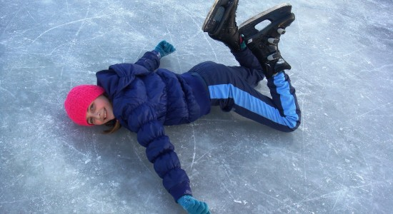 Girl laying down on ice with ice skates on
