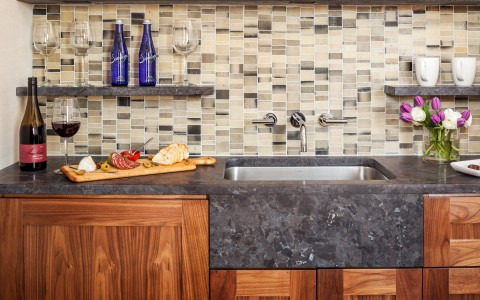Kitchen granite countertop with wine, cutting board with cheese & wooden cabinets