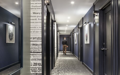 Hallway of room entrances with carpet designed with scattered letters on floor