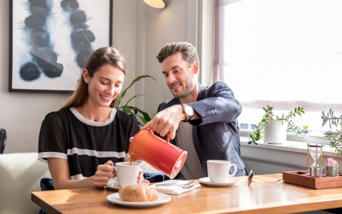 Man pouring coffee into womans mug
