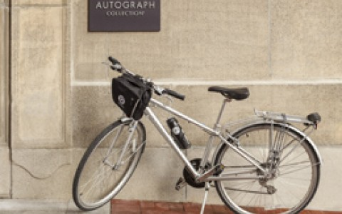 Silver bicycle parked next to autograph collection sign on building
