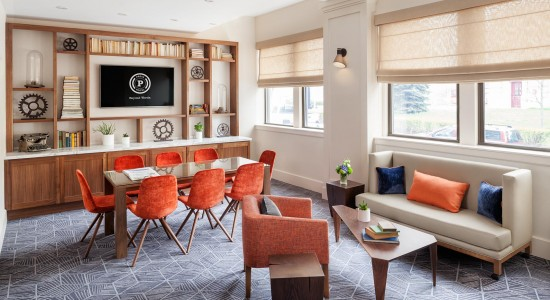 Living space with sofas & coffee table next to wooden dining table with orange chairs