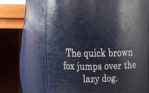 The quick brown fox jumps over the lazy dog stitched onto the back of a leather desk chair