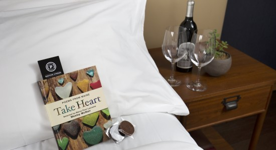 Wine glasses on nightstand next to bed with book