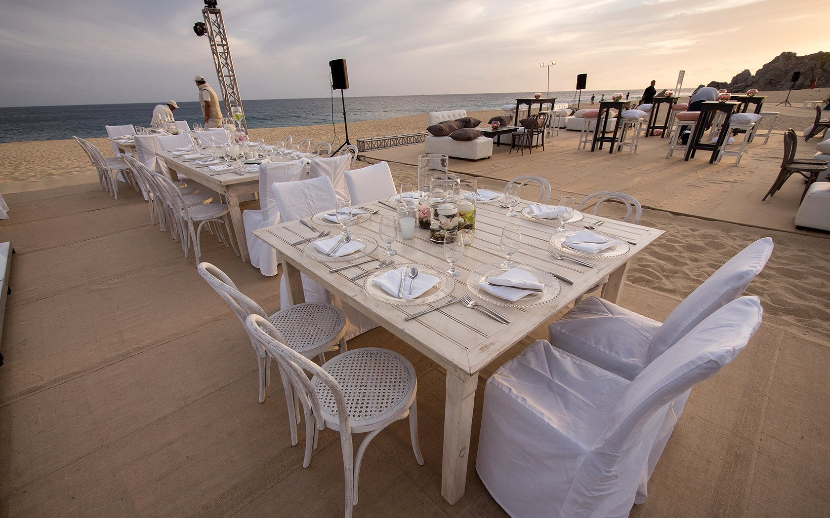 white wood tables set up on the beach for a reception