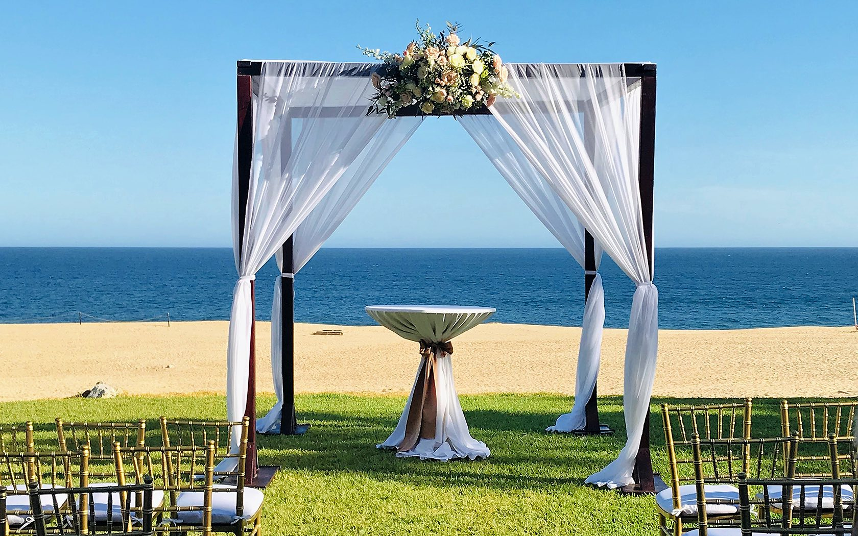 wedding arch with white linen over looking ocean