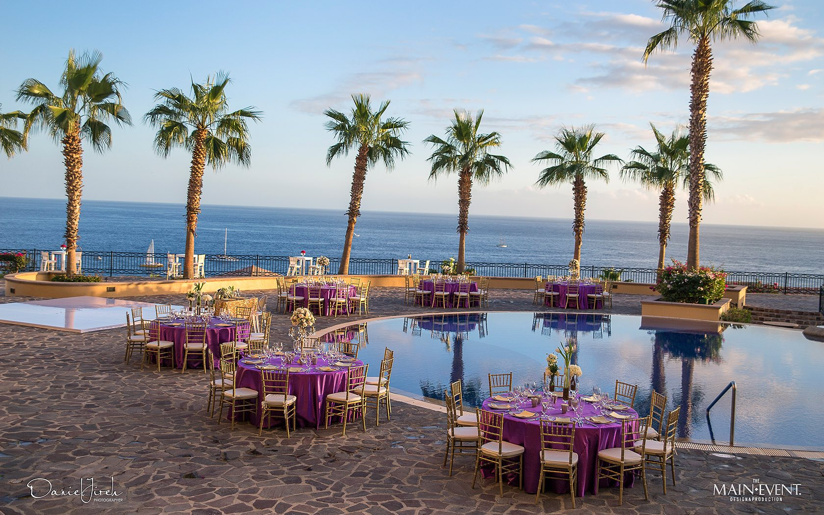 tables around pool with palm trees and ocean views