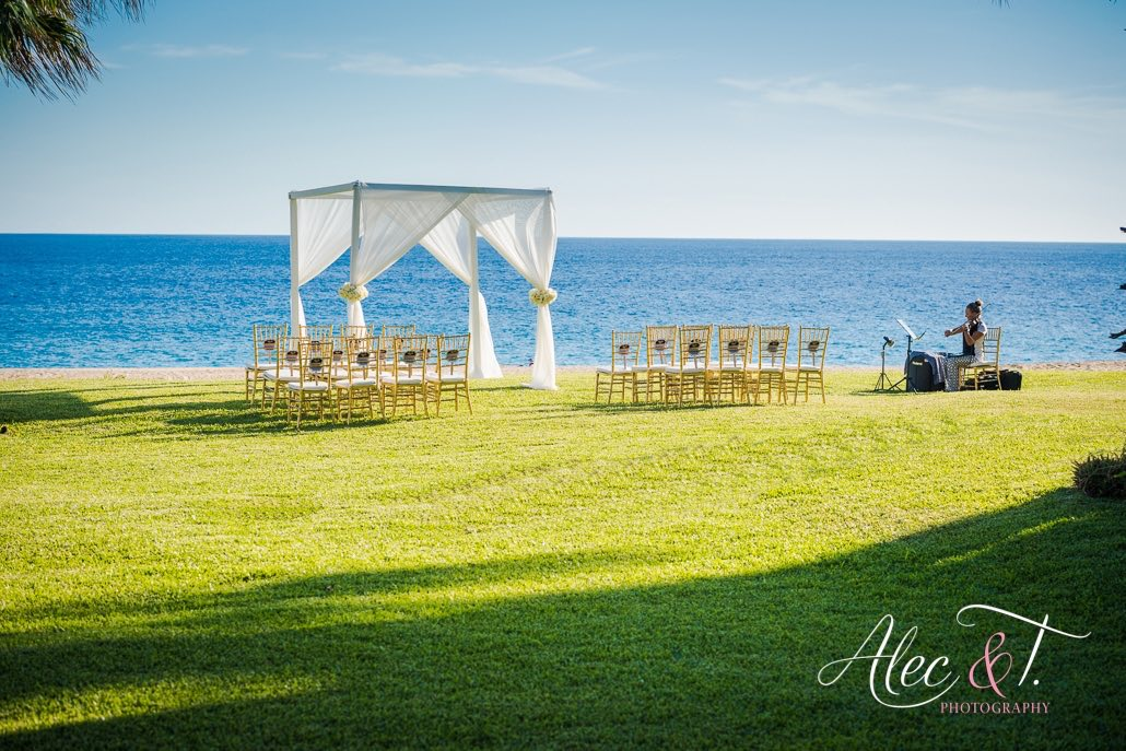 beach wedding ceremony with chairs and arch overlooking water