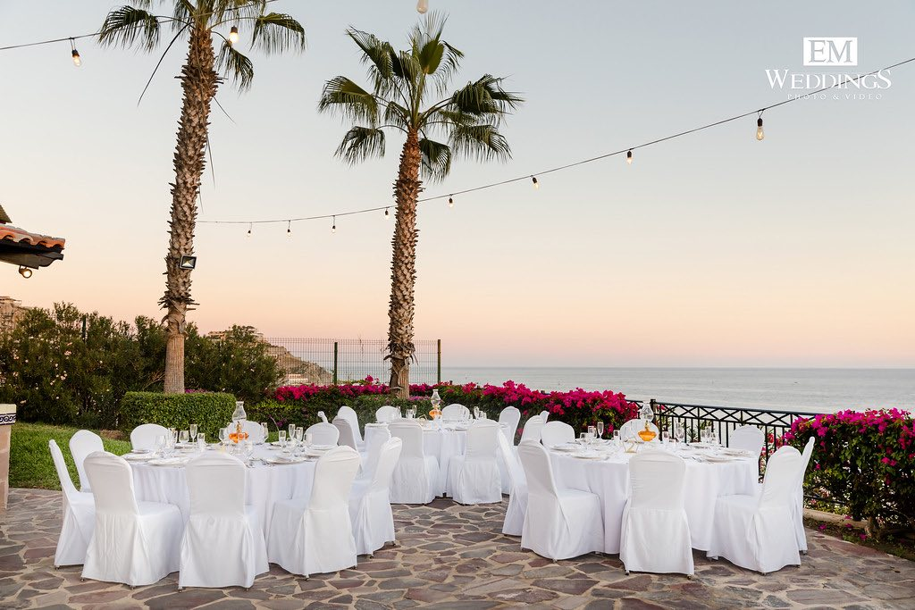 white tables and chairs in outside venue during sunset