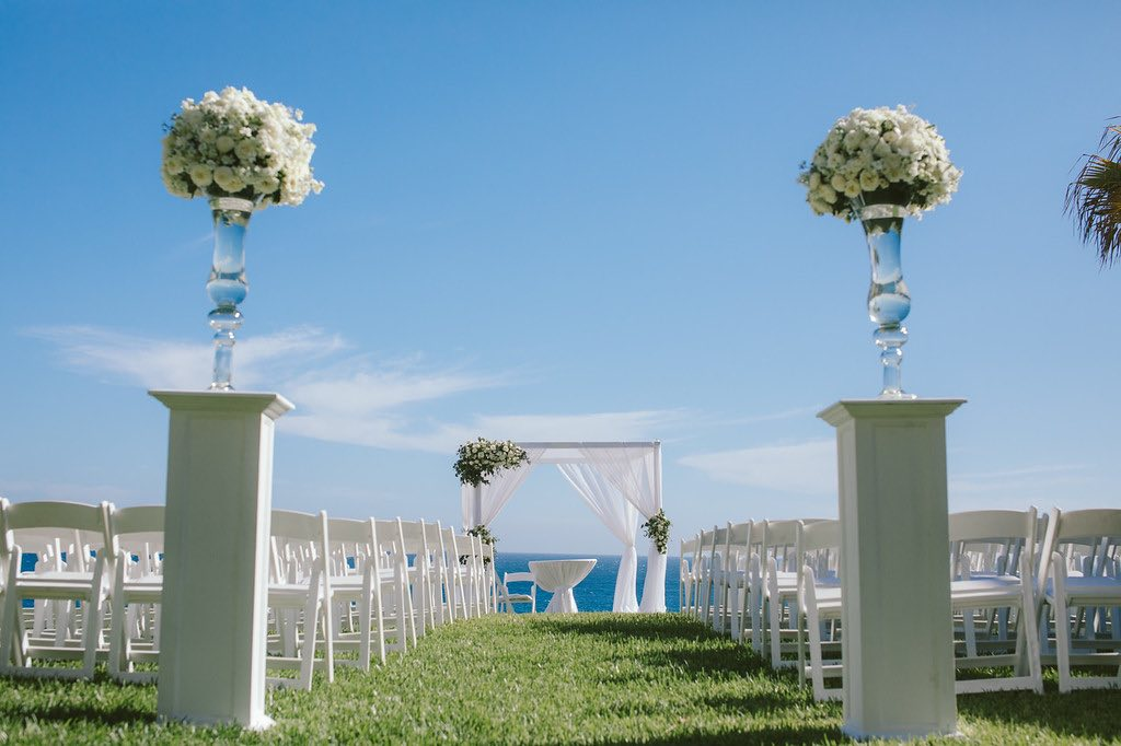 walkway view of wedding ceremony set up with white chairs and arch