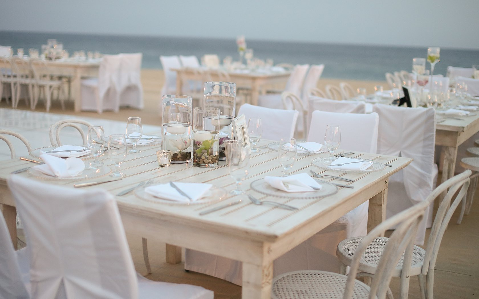 white wood table on beach plated for a reception
