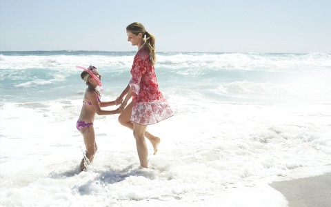 women and child playing in ocean
