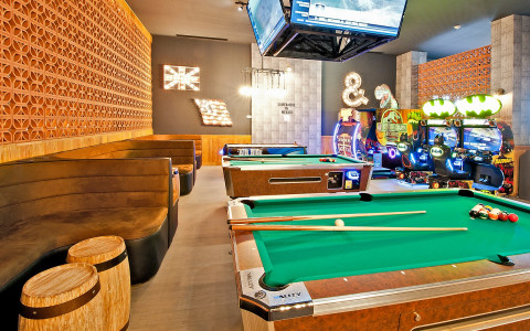 pool tables with arcade games in the back