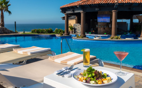 chair with food and drinks overlooking pool and ocean