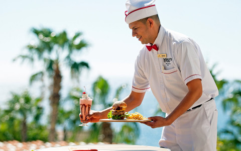 man in uniform serving hamburger and milkshake