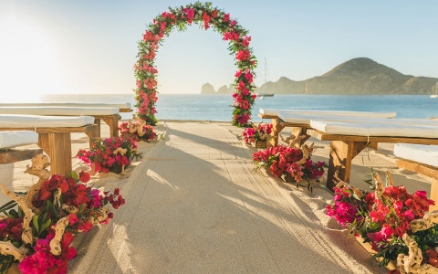 red flower wedding arch by the ocean