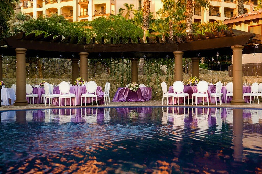tables with purple linen surrounding pool
