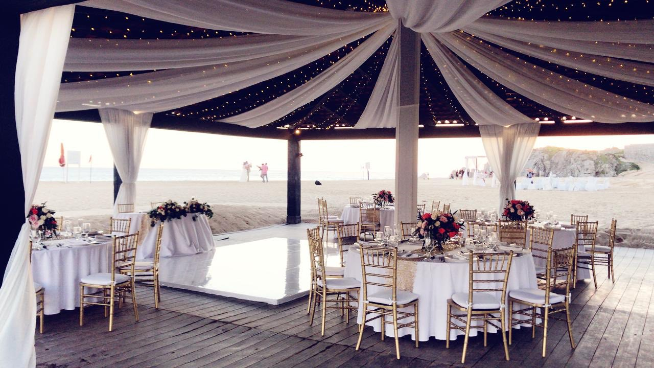 white linen in gazebo with tables on wood floor