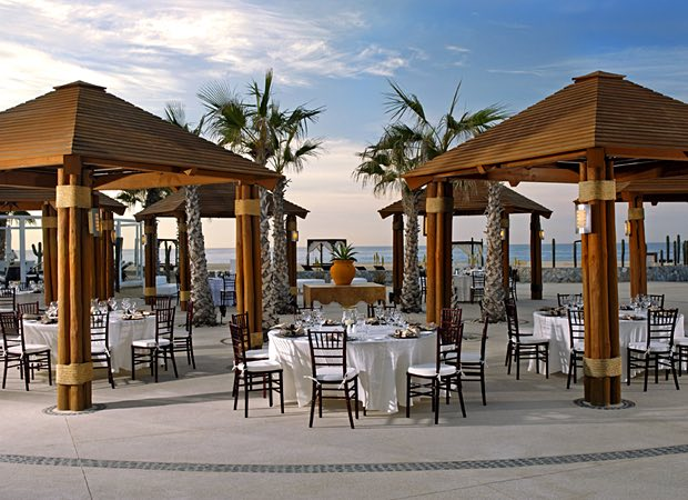 outside venue with huts covering tables overlooking ocean