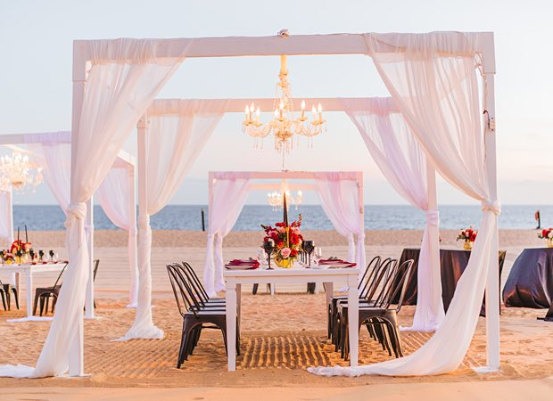 linen canopy with lighting and tables set up on beach