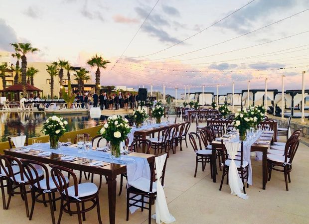 multiple tables set up with white flowers outside during sunset