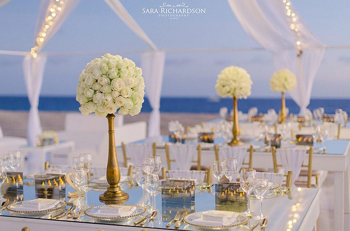 wedding table with white flowers on beach